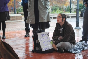 A protester from the Occupy movement listens to a fellow demonstrator at Market Square in Old Town Alexandria Tuesday after walking about 100 miles from Richmond. (David Sachs)